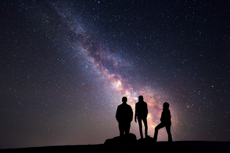 Milky Way. Night sky with stars and silhouette of a happy family with raised-up arms Reklamní fotografie - 48174767