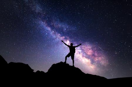 天の川。上げる腕を持つ男のシルエットと星夜の空。