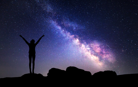 Milky Way. Night sky with stars and silhouette of a woman with raised-up arms. Stock Photo
