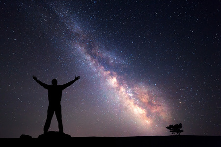 Milky Way. Night sky with stars and silhouette of a man with raised-up arms.