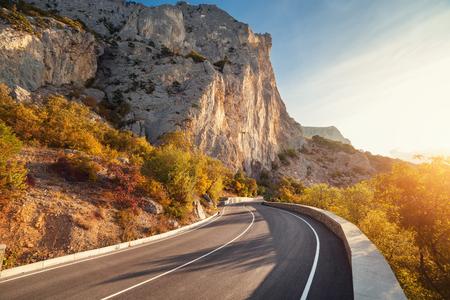 Asphalt road in autumn forest at sunrise. Crimean mountains. 免版税图像