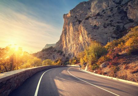 アスファルト道路日の出秋の森。クリミア山脈。