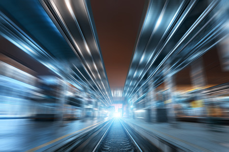 railway transport: Railway station at night with motion blur effect. Cargo train platform in fog. Railroad