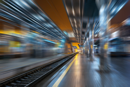 urban colors: Railway station at night with motion blur effect. Cargo train platform in fog. Railroad