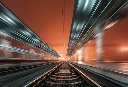 railroad station platform: Railway station at night with motion blur effect. Cargo train platform in fog. Railroad