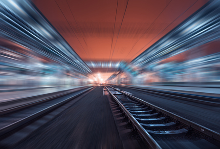light color: Railway station at night with motion blur effect. Cargo train platform in fog. Railroad