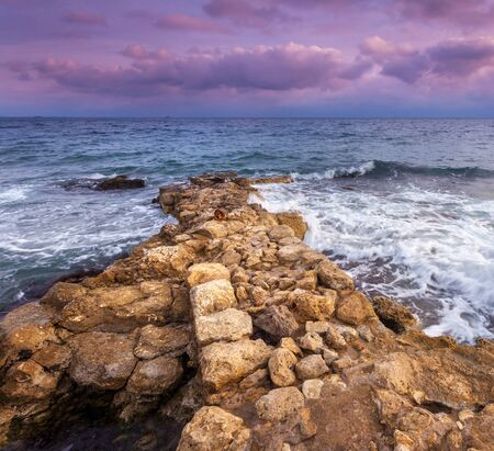 Sea waves with rocks on the beach at sunset. Beatuful landscape Stock Photo