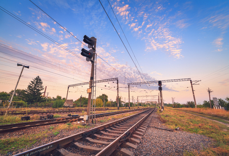 railroad station platform: Train platform and traffic light at sunset. Railroad. Railway station