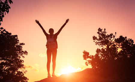 woman hands up: Silhouette of a happy young woman with backpack and raised arms at the sunset in mountains at summer. Nature background Stock Photo