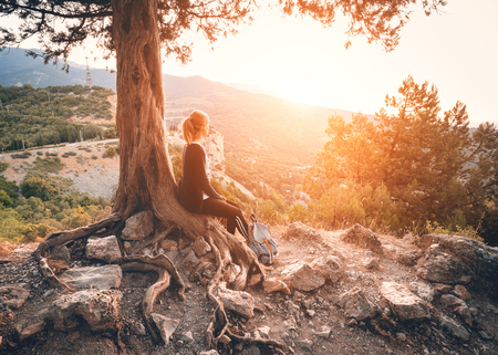 Young woman sitting on the mountain near old tree at sunset. Summer natural landscape