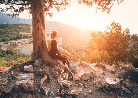 Mujer joven sentada en la montaña cerca del árbol de edad en la puesta del sol. paisaje natural del verano