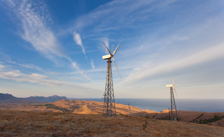 energy fields: Wind turbine generating electricity in mountains at sunset. Stock Photo