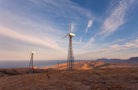 wind farm: Wind turbine generating electricity in mountains at sunset. Stock Photo