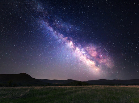 hill: Landscape with Milky Way. Night sky with stars at mountains. Stock Photo