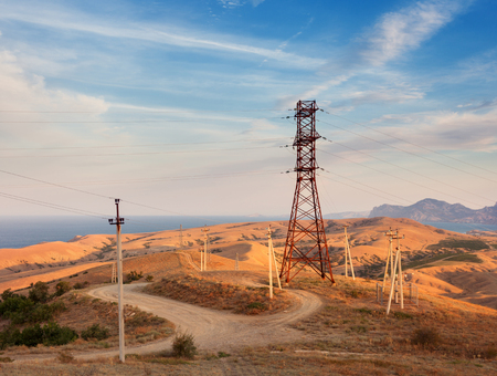 metal grid: High voltage tower in mountains on the background of colorful sky at sunset.  Electricity pylon system. Summer evening. Industrial landscape Stock Photo