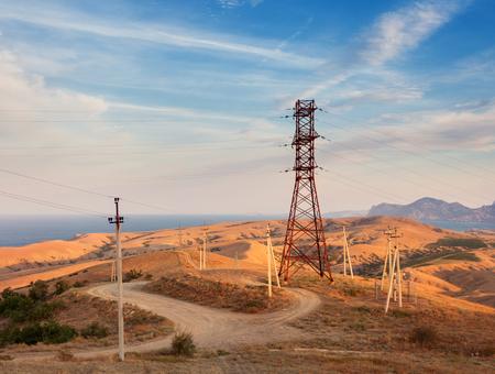 Hochspannungs-Turm in den Bergen auf dem Hintergrund der bunten Himmel bei Sonnenuntergang. Strommast-System. Sommerabend. Industrielandschaft