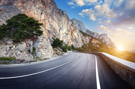 Beautiful winding mountain road with a perfect asphalt with high rocks and colorful sunset in summer.