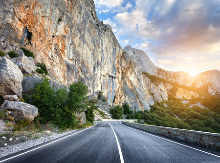 Beautiful mountain road with a perfect asphalt, high rocks, colorful sky at sunset in summer.