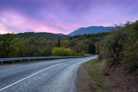 country roads: Mountain winding road passing through the forest with colorful sky at sunset in summer