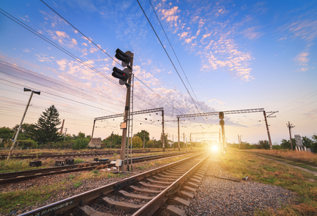 railway: Train platform and traffic light on the background of colorful blue sky at sunset. Railroad. Railway station.