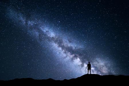 Paisaje con la Vía Láctea. cielo nocturno con las estrellas y la silueta de un hombre feliz que se coloca en la colina. Foto de archivo