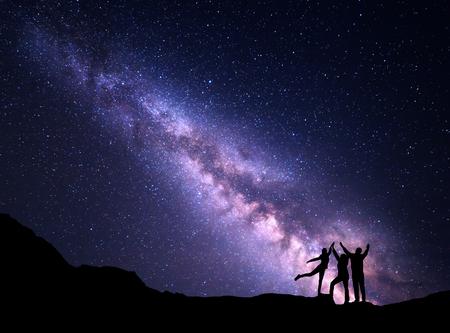 紫の天の川のある風景します。夜星空と山に上げる腕を持つ幸せな家族のシルエット。美しい宇宙。空間の背景