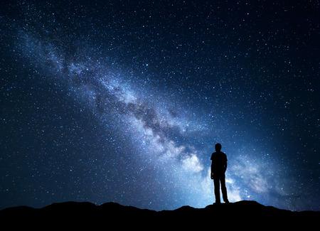 Landschap met blauwe Melkweg. Nachthemel met sterren en silhouet van een gelukkig man op de berg. Prachtig universum. Ruimte achtergrond