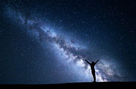 Landscape with blue Milky Way. Night sky with stars and silhouette of a standing sporty girl with raised-up arms. Beautiful Universe. Space background
