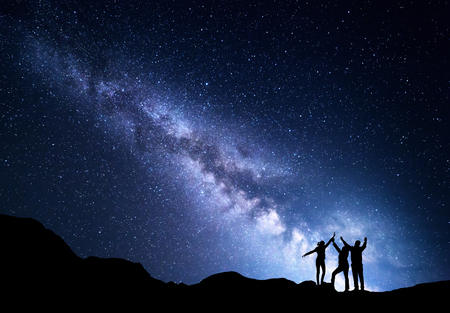 Landscape with blue Milky Way. Night starry sky with silhouette of a happy family with raised-up arms on the mountain. Beautiful Universe. Space background Standard-Bild