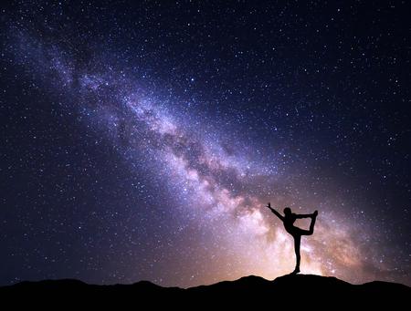 Paisaje con púrpura Vía Láctea. cielo nocturno colorido con las estrellas y la silueta de una chica deportiva de pie con los brazos levantados arriba en la montaña. Hermosa Universo. El espacio de fondo Foto de archivo