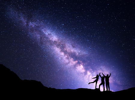 Landscape with purple Milky Way. Night starry sky with silhouette of a happy family with raised-up arms on the mountain. Beautiful Universe. Space background