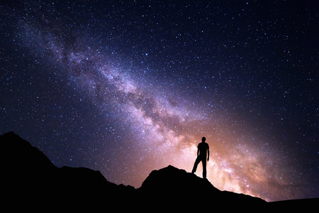 Landscape with Milky Way. Night sky with stars and silhouette of a happy man on the rock. Beautiful Universe. Space background Archivio Fotografico