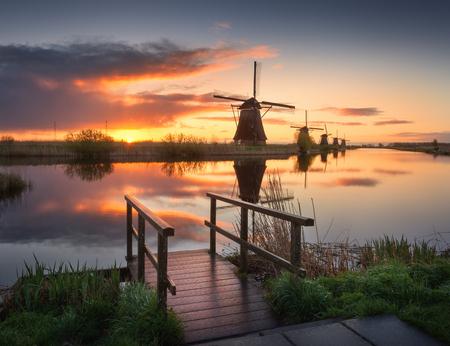 Landschap met prachtige traditionele Nederlandse windmolens in de buurt van het water grachten met blauwe hemel en wolken weerspiegeling in het water. Kleurrijke gele zonsopgang in de beroemde Kinderdijk, Nederland in het voorjaar