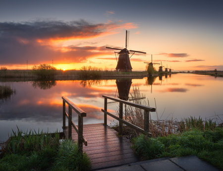 Landscape with beautiful traditional dutch windmills near the water canals with blue sky and clouds reflection in water. Colorful yellow sunrise in famous Kinderdijk, Netherlands in spring