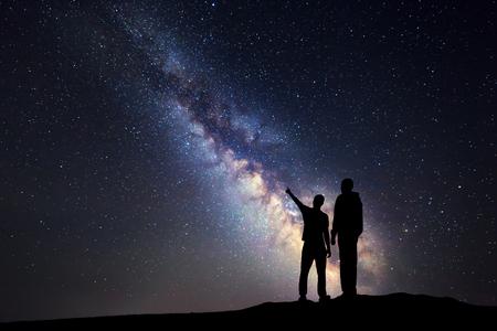 Silueta de un padre y un hijo que señala el dedo en la noche de cielo estrellado en el fondo de la Vía Láctea. Familia. colorido paisaje nocturno. Hermosa Universo. Espacio. Antecedentes de viaje con el cielo lleno de estrellas
