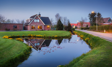 dutch canal house: Landscape in dutch village with beautiful house reflected in water canal, courtyard with green grass , yellow flowers and road with illumination at dusk in Netherlands.