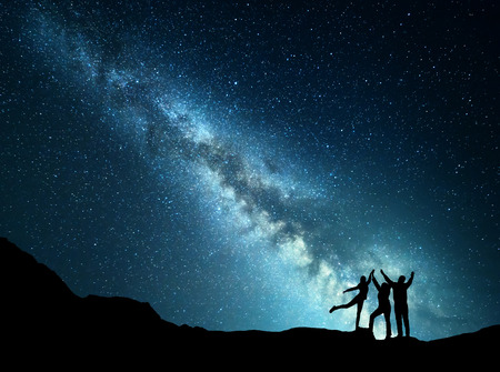 Landscape with colorful green Milky Way. Night starry sky with silhouette of a sporty happy family with raised-up arms on the mountain. Beautiful Universe. Space background 免版税图像