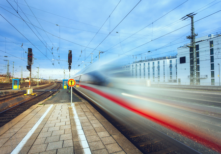 High speed passenger train on tracks in motion at sunset. Blurred commuter train. Railway station in Nuremberg, Germany. Railroad with vintage toning