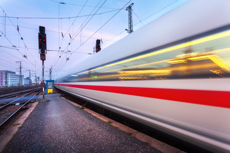 High speed passenger train on railroad track in motion at night. Blurred commuter train. Railway station in Nuremberg, Germany. Industrial landscape