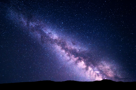 Landscape with purple Milky Way. Night sky with stars and hills at summer. Beautiful universe. Space background Banco de Imagens