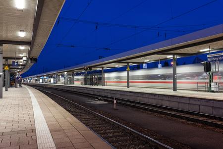 railroad station platform: Modern railway station with high speed passenger train on railroad track in motion. Railway platform at night  in Nuremberg, Germany. Fast train. Stock Photo