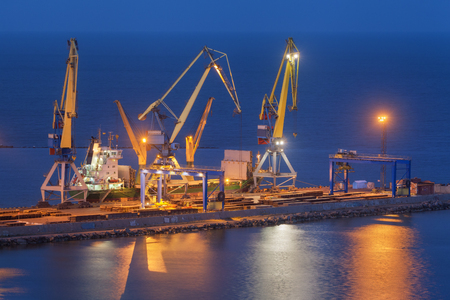 Cargo freight ship with working cranes bridge in sea port at twilight. Sea commercial port at night in Mariupol, Ukraine. Industrial view. Cargo port, logistic