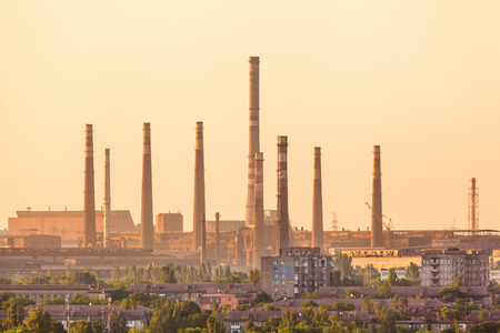 City buildings on the background of steel factory with smokestacks at colorful sunset. metallurgical plant. steelworks, iron works. Heavy industry in Europe. Air pollution from smokestacks. Industrial landscape