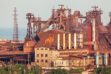 steelworks: Rusty steel factory with smokestacks at sunset. metallurgical plant. steelworks, iron works. Heavy industry in Europe. Air pollution from smokestacks, ecology problems. Industrial landscape