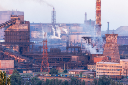 steelworks: Industrial landscape in Ukraine. Steel factory at sunset. Pipes with smoke. Metallurgical plant. steelworks, iron works. Heavy industry in Europe. Air pollution from smokestacks, ecology problems. Stock Photo