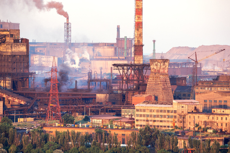 metallurgical: Industrial landscape in Ukraine. Steel factory with smog at sunset. Pipes with smoke. Metallurgical plant. steelworks, iron works. Heavy industry. Ecology problems, atmospheric pollutants.