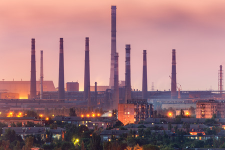 steel works: City buildings on the background of steel factory with smokestacks at night.  Metallurgical plant with chimney. steelworks, iron works. Heavy industry. Air pollution, smog. Industrial landscape