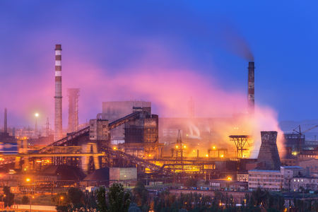 steel works: Metallurgical plant at night. Steel factory with smokestacks . Steelworks, iron works. Heavy industry in Europe. Air pollution from smokestacks, ecology problems. Industrial landscape at twilight
