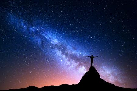 天の川の夜の風景。山の頂上に上がっている腕を持つ、立っている人のシルエット。美しい宇宙。青い夜輝く空と街の光と背景を旅行します。