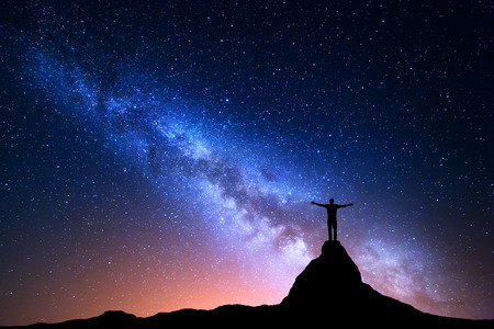 Night landscape with Milky Way. Silhouette of a standing man with raised up arms on the mountain peak . Beautiful Universe. Travel background with blue night starry sky and city lights